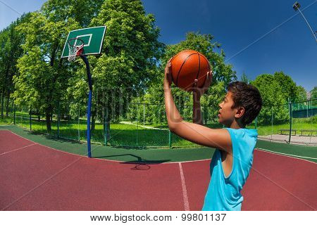 Arabian boy throwing ball in basketball goal on the playground outside during sunny summer day poster