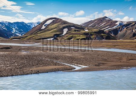 Summer flood of meltwater blocks the way to tourist camping. The picturesque valley in national park Landmannalaugar, Iceland