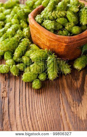 Fresh green hops on a wooden desk, served in bowl. Low depth of focus