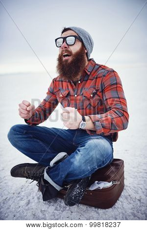 hyped up hobo like hipster with manly awesome beard and sunglasses sitting on retro suicase in empty desolate salt flats