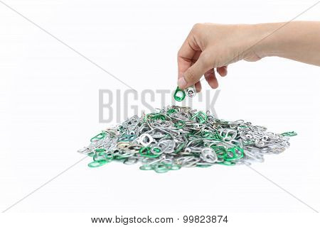 Hand Holding Aluminum Cap Can Over A Pile Of Cap Can