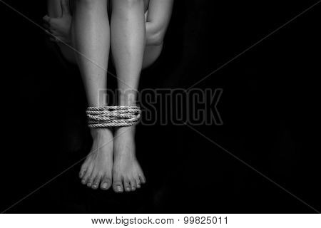 Feet Of A Missing Kidnapped, Abused, Hostage, Victim Woman Tied Up With Rope In Emotional Stress And