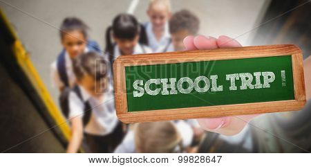 The word school trip! and hand showing chalkboard against cute schoolchildren getting on school bus