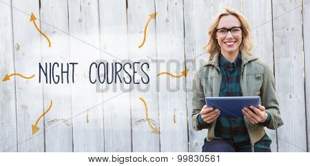 The word night courses against smiling blonde in glasses using tablet pc