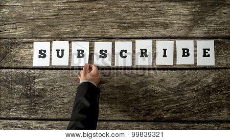Overhead View Of Businessman Arranging Nine White Cards With Letters Into A Word Subscribe