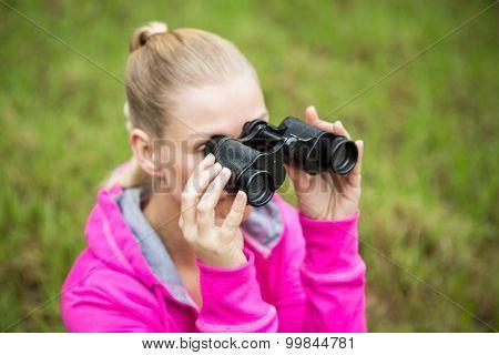 Upward view of a female hiker looking through the binoculars poster