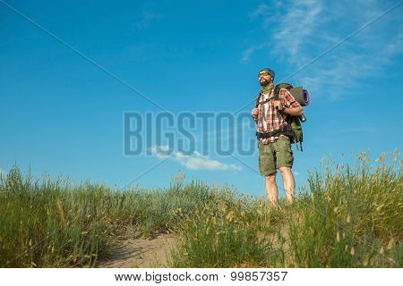 Young caucasian man with backpack standing on the top of hill