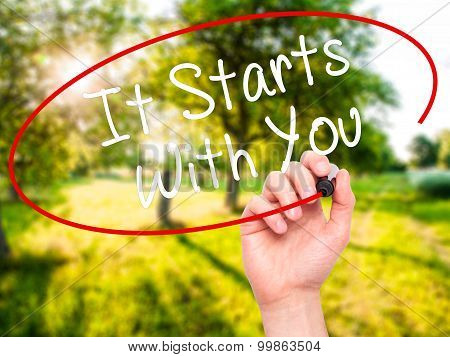 Man Hand writing It Starts With You with black marker on visual screen.