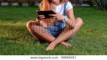 Young woman enjoying her time in park with tablet computer