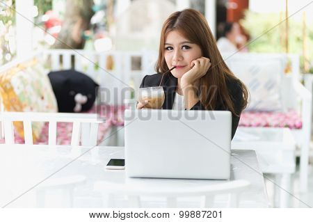 Asia Young Business Woman Sitting In A Cafe With Laptop And Iced Coffee