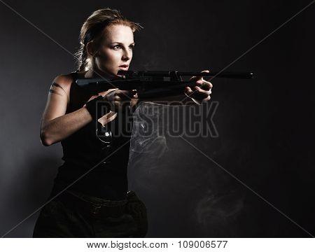 Sexy woman with rifle on dark studio shot