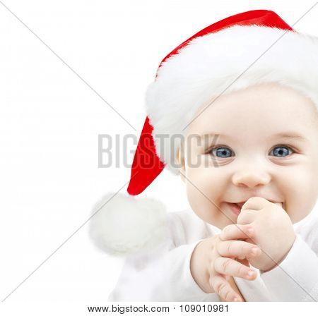 christmas, babyhood, childhood and people concept - happy baby in santa hat over white