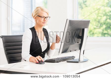 Beautiful female office worker having a break by the computer having a cup of coffee.