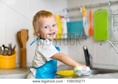 Toddler child washing dishes in kitchen. Little boy having fun with helping to his mother with house