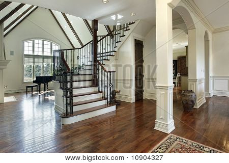Foyer in luxury home with arched entry into dining room poster