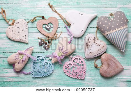Different Decorative  Hearts On Turquoise Painted Wooden Background.