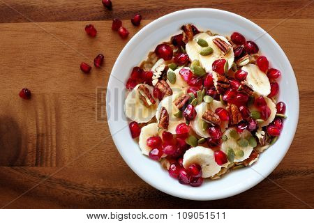 Bowl Of Healthy Breakfast Oatmeal With Pomegranate, Bananas, Seeds And Nuts, Overhead View On Wood