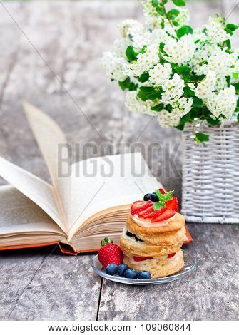 puff pastry with berries old book and beautiful bouquet of white flowers