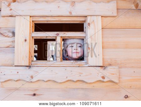boy looks out the window of a wooden house