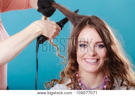 Hairdresser Curling Woman Hair With Iron Curler.