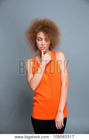 Portrait of confused puzzled unsure pretty curly young woman on gray background