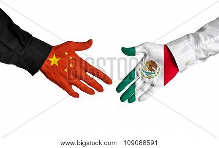 China and Mexico leaders shaking hands on a deal agreement