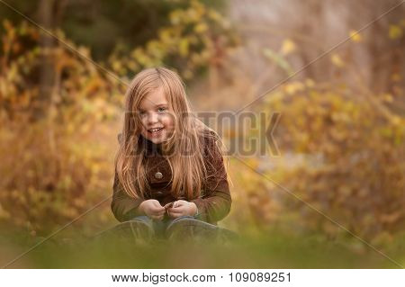 outdoor portrait of a laughing beautiful little girl sitting on a grass