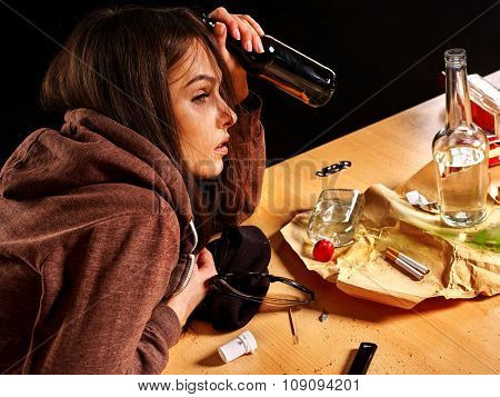 Drunk girl holding bottle of alcohol. Soccial issue alcoholism. Side view.