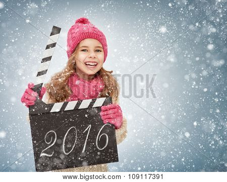 child girl in winter clothes holding clapper board in hands. new year concept.