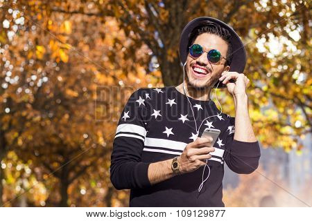 Young man listening to music and texting on his smartphone