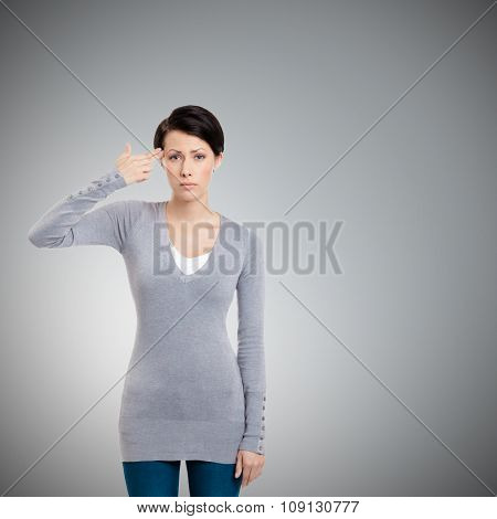 Disappointed girl shows hand gun gesture, isolated on grey
