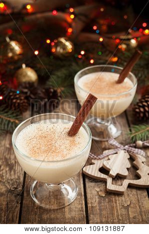 Eggnog christmas seasonal traditional non alcohol egg liqueur in two glass cups on vintage wooden ta