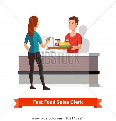 Sales clerk handing tray to a woman customer
