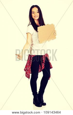 Beautiful young woman hitch hiking with empty cardboard.