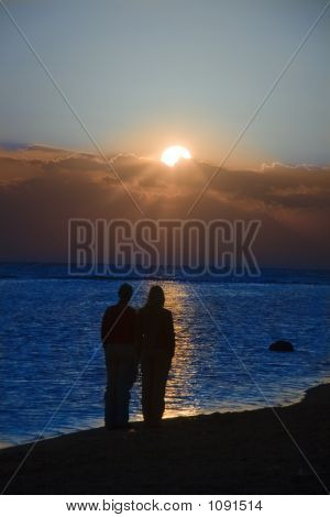 a couple meeting sunrise on the beach poster
