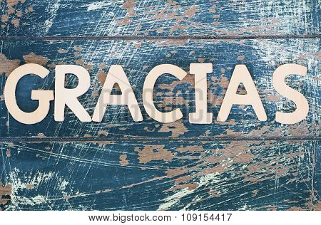 Gracias (thank you in Spanish) written on rustic wooden surface