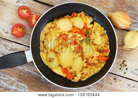 Omelette with potatoes, onions, red pepper and sweetcorn in frying pan