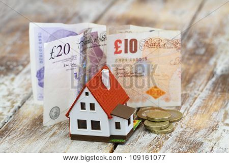 Model house in front of British pound notes and coins