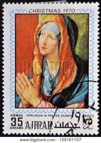 AJMAN - CIRCA 1970: Stamp printed in Ajman shows Virgin in prayer by Durer circa 1970