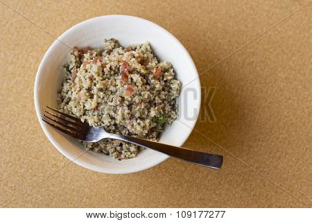 Bowl of fresh organic quinoa salad in large white bowl