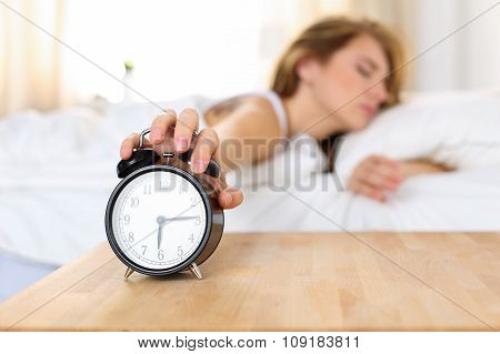 Sleepy young woman trying kill alarm clock while bury face in pillow. Early wake up not getting enough sleep getting work concept. Female stretching hand to ringing alarm willing turn it off poster