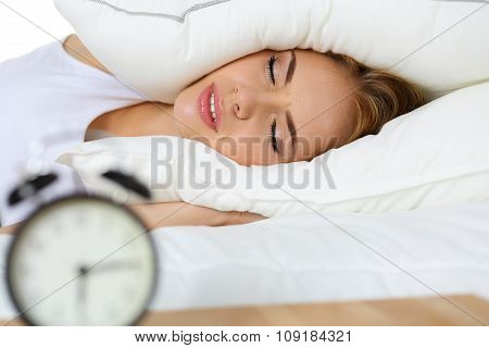 Young Beautiful Blonde Woman Lying In Bed Suffering From Alarm Clock Sound