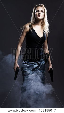 Sexy woman holding gun with smoke.  studio shot