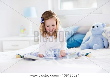 Little Girl Playing With Toy And Reading A Book In Bed