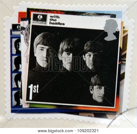 a postage stamp printed in Great Britain showing an image of The Beatles With The Beatles album cove