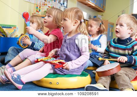 Group Of Pre School Children Taking Part In Music Lesson