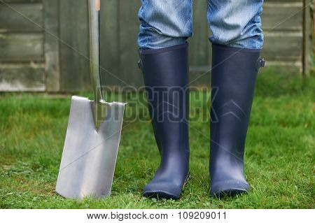 Close Up Of Man Wearing Wellingtons Holding Garden Spade