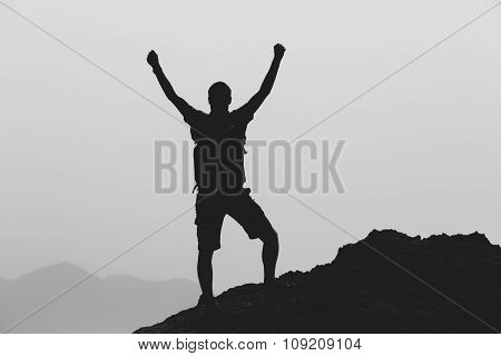 Success achievement climbing or hiking accomplishment business concept with man celebrating arms up