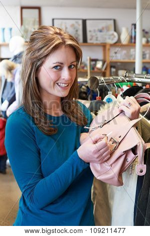 Female Shopper In Thrift Store Looking At Handbag