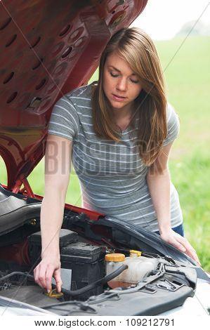 Broken Down Female Motorist Looking At Car Engine